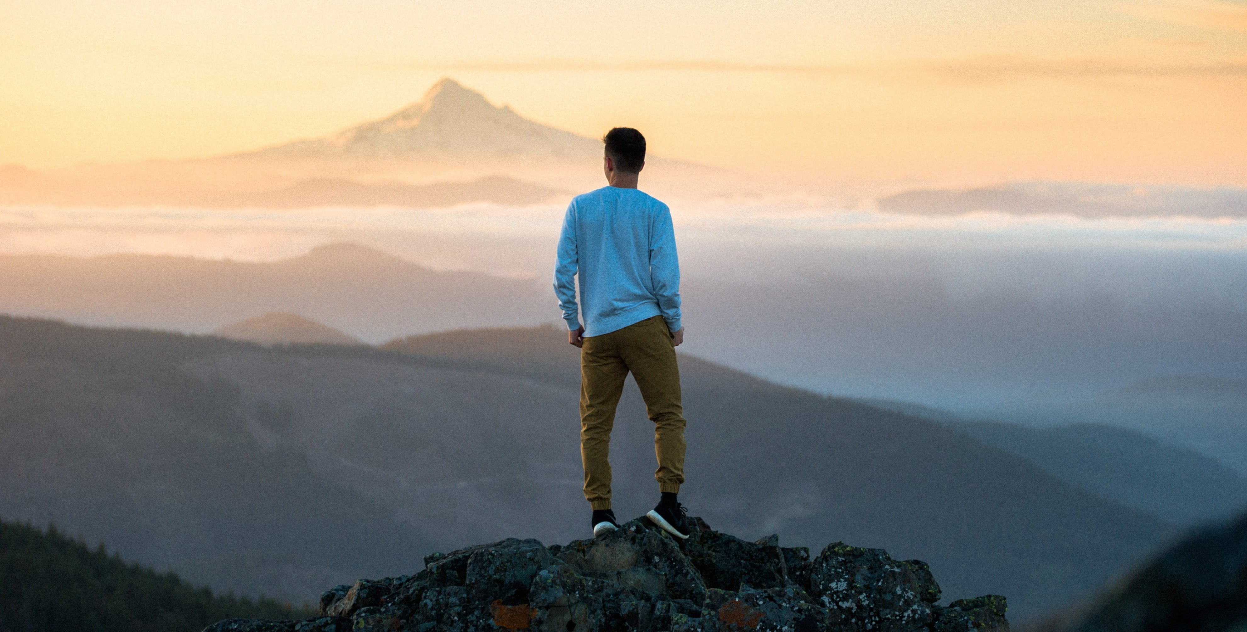 Young man standing on a mountain top looking out at the view